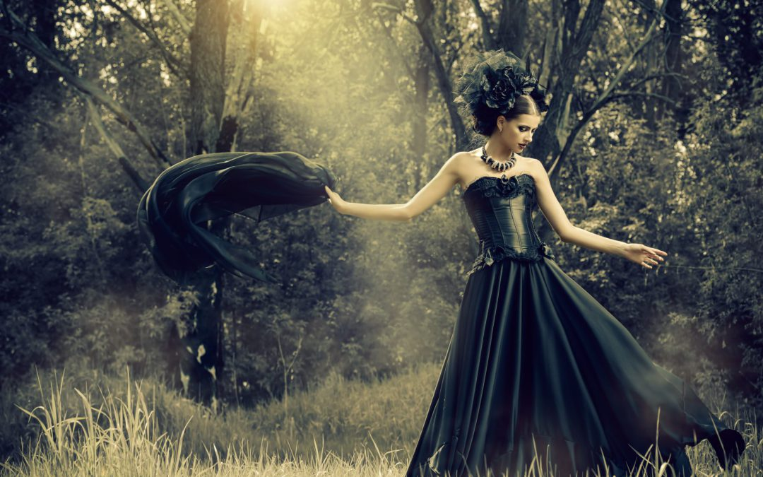 Highly made-up female model wearing flamboyant black dress in forest
