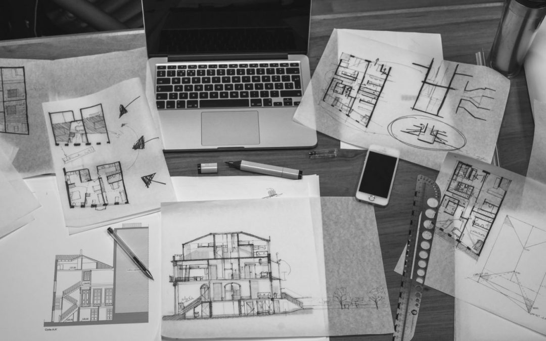 Black and white image of desk with blueprints and laptop