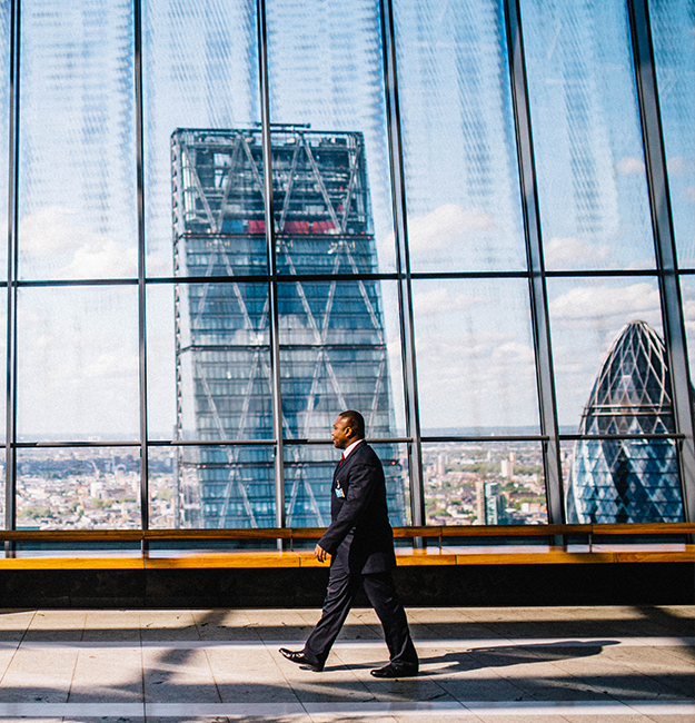 Well dressed business man walking past large windowed building with view of city