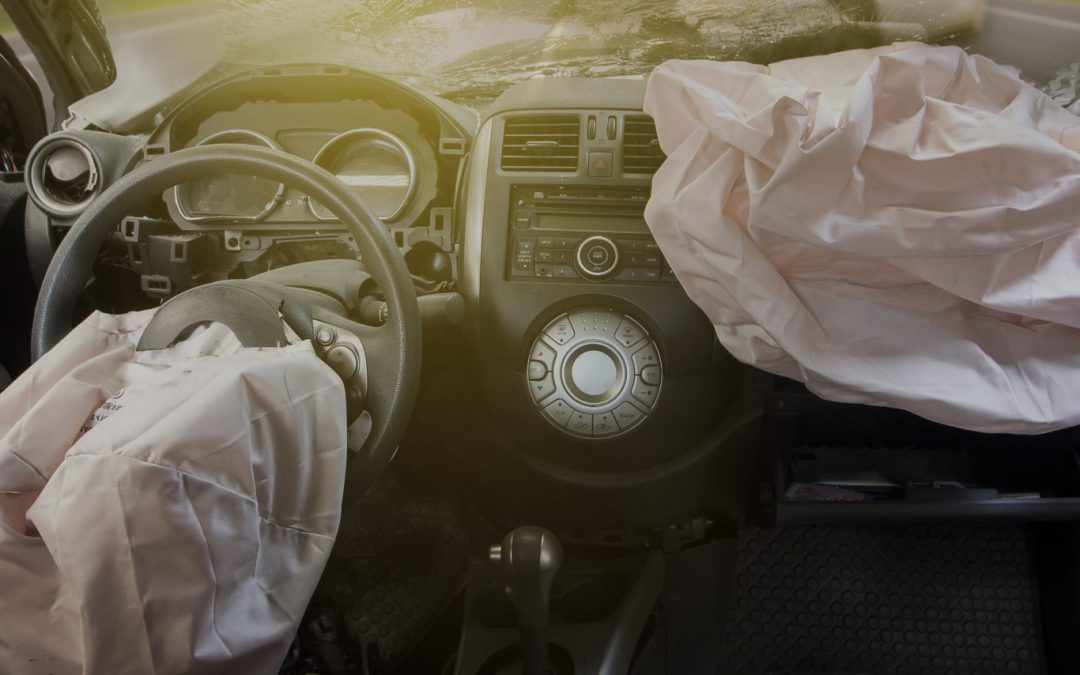 Crashed car dashboard with two deflated airbags after deployment