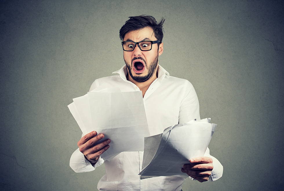 Man in white shirt and glasses holding bills and looking horrified