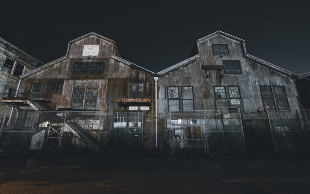 Two large run-down warehouses at night