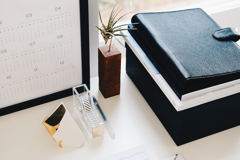 A tidy desk with a calendar, black diary and a small plant ornament.