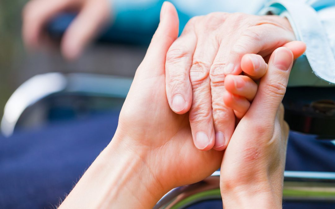 Close up of caring nurse's hands holding an older lady's hand