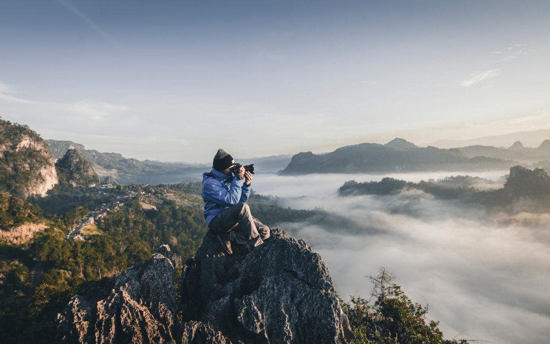 Photographer at the top of a craggy peak taking picture of mountain