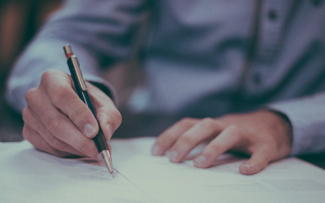 Man in blue shirt signing forms with black and gold pen