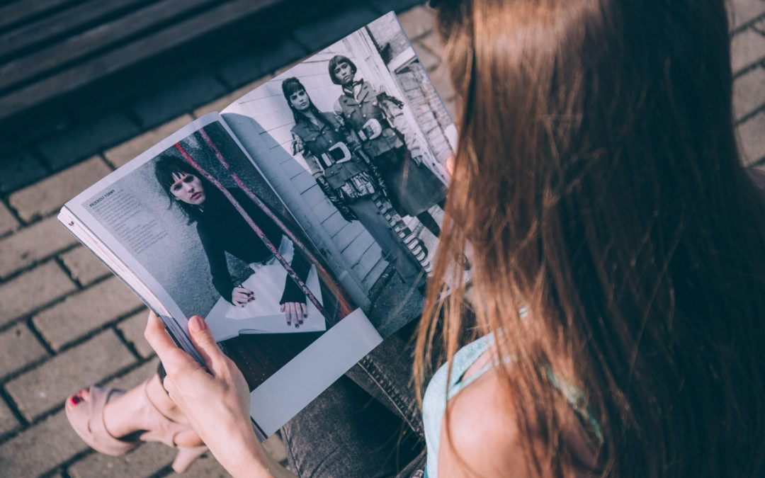 View over young lady's shoulder while she sits reading a fashion magazine